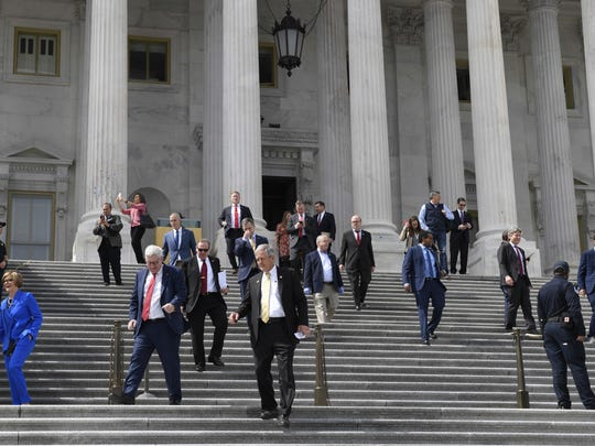 Members of the House of Representatives walk down the steps of Capitol Hill in Washington, Friday, March 27, 2020, after passing a coronavirus rescue package. Acting with exceptional resolve in an extraordinary time, the House rushed President Donald Trump a $2.2 trillion rescue package Friday, tossing a life preserver to a U.S. economy and health care system left flailing by the coronavirus pandemic. (AP Photo/Susan Walsh)