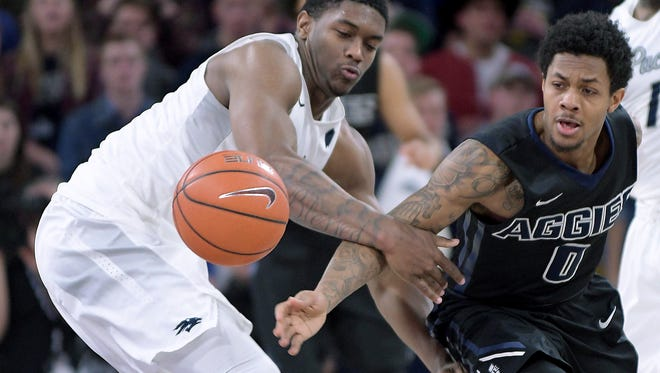 Nevada's Cameron Oliver, left, and Utah State's Shane Rector scramble for a loose ball during their game earlier this month.