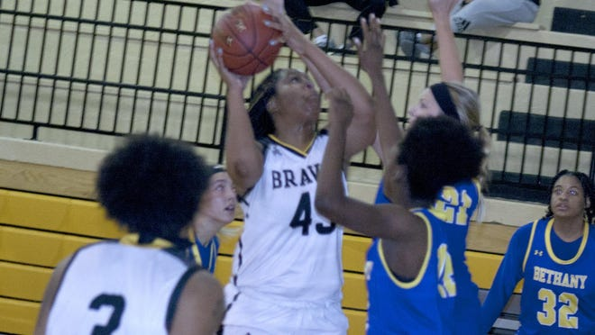 Ottawa University junior forward Kanecia Payne powers up a shot over Bethany defenders. Payne scored a team-best 13 points in the 66-57 loss.