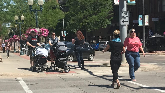 Pedestrians walk across 10th Avenue along Phillips Avenue in downtown Sioux Falls Thursday afternoon.