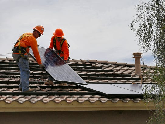 Electricians install solar panels on the roof of a