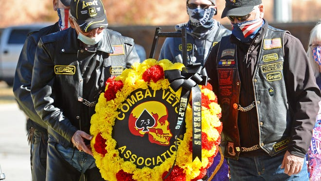 Veterans Joe Robine, left, and John Bartlett place the Combat Veterans Motorcycle Association wreath during a Veterans Day program at the National Cemetery in Fort Smith on Wednesday, Nov. 11.