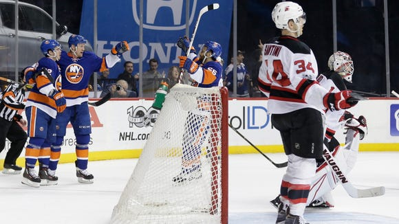 New York Islanders' Jason Chimera (25), Anthony Beauvillier (72) and Joshua Ho-Sang (66) celebrate a goal by Beauvillier as New Jersey Devils goalie Keith Kinkaid (1) and Steven Santini (34) looks away during the second period of an NHL hockey game Friday, March 31, 2017, in New York. (AP Photo/Frank Franklin II)