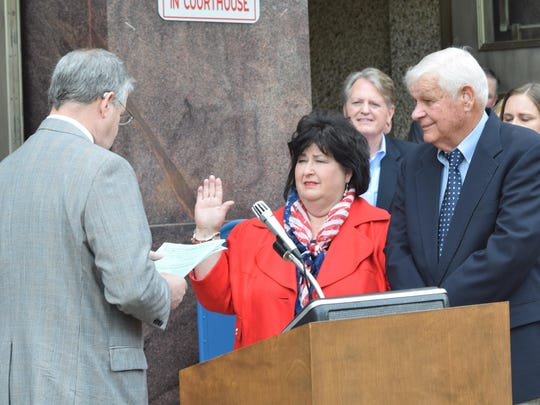 Ninth District Judge Tom Yeager (left) administers the oath of office for Lin Dyess Stewart (center) as she became Rapides Parish registrar of voters Thursday. With her is her husband, Charles Stewart (right).