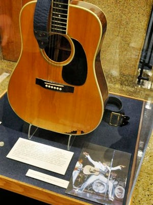 FILE - This April 22, 2013, file photo, shows the slightly smashed acoustic guitar played by Elvis Presley during the final tour before his death in 1977 on display at the National Music Museum in Vermillion, S.D. Larry Moss, a collector, has asked a federal judge to declare him the owner of the guitar claiming the museum did little or no due diligence to determine whether donor Robert Johnson had rights over the guitar. (AP Photo/Dirk Lammers, File)