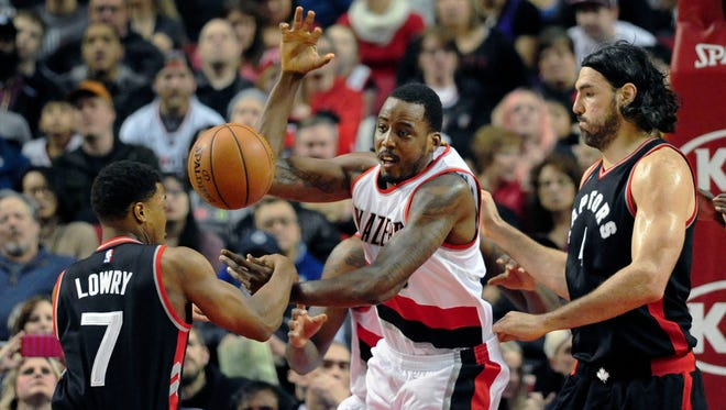 Toronto Raptors guard Kyle Lowry (7) knocks the ball away from Portland Trail Blazers forward Al-Farouq Aminu (8) as Toronto Raptors forward Luis Scola (4) closes in during the first half of an NBA basketball game in Portland, Ore., Thursday, Feb. 4, 2016.