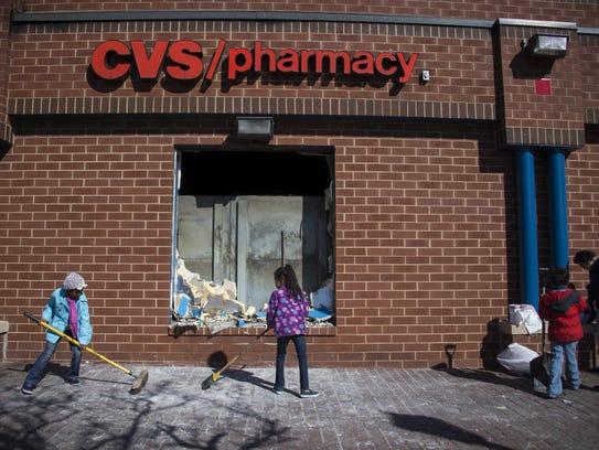 Children sweep up the area outside a CVS Pharmacy.