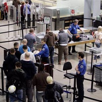 In this Monday, March 30, 2009 file photo, passengers line up at a TSA security check at Minneapolis-St. Paul International Airport.