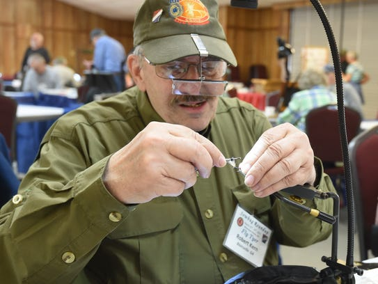 Robert Kern of Blairsville, Ga., gets a closer look at the fly he is crafting during the first day of the 2017 Sowbug Roundup.
