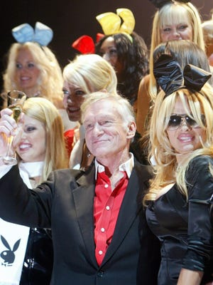 Playboy founder and publisher Hugh Hefner gives a toast next to his guest, former Playboy playmate Pamela Anderson, right, during the 50th anniversary of Playboy party in New York, on Dec. 4, 2003.