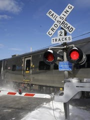 A train passes through the intersection where an SUV was struck by a Metro-North Railroad train in Valhalla on Thursday.