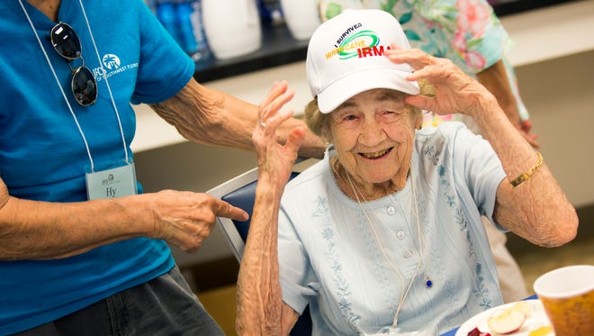"""Vivian Marra adjusts her """"I survived Hurricane Irma"""" hat Wednesday, Sept. 20, 2017, at the Naples Senior Center. Marra celebrated her 99th birthday the week before the hurricane and evacuated. On her way back into town, her daughter bought her the hat at a gas station."""