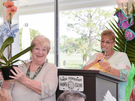 Mary Lou Lemaire, left, holds an orchid as Cheri Mabry