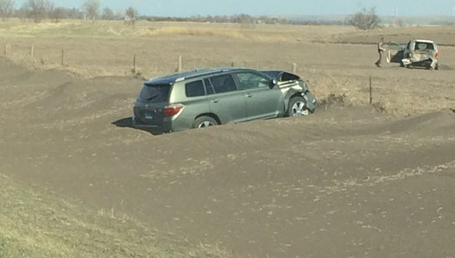 A crashed car with more than a foot of dirt drifted around it on Sunday after blackout conditions during a dust storm.
