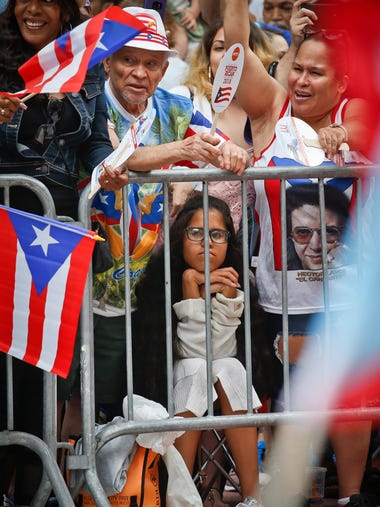 Rosary Santos, 14, center, sits between her grandfather