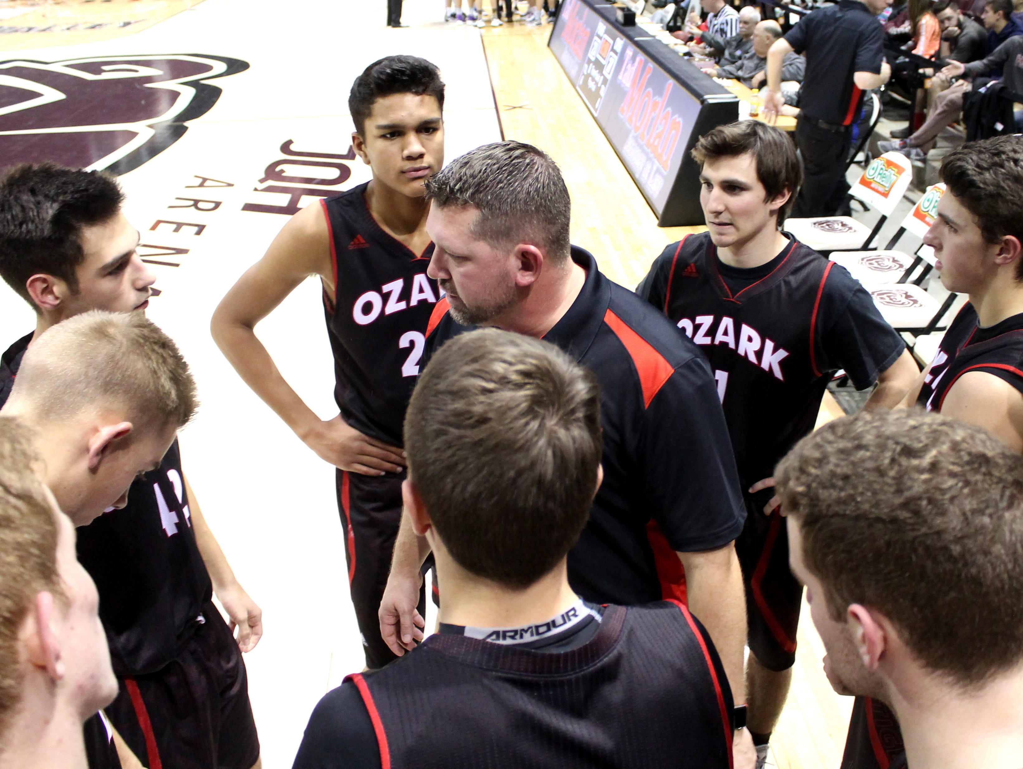 The Ozark Tigers surround coach Mark Schweitzer during the 2016 Greenwood Blue and Gold Tournament at JQH Arena.
