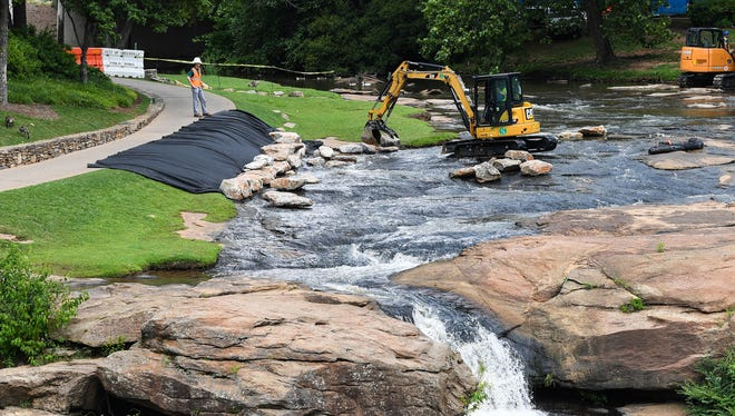 The City of Greenville work on a stream bank restoration project in Falls Park at the top of the falls on Monday, June 19, 2017.