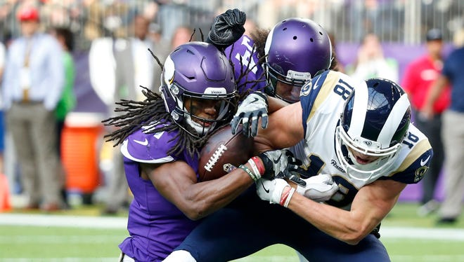 Minnesota Vikings strong safety Anthony Harris, left, strips the ball from Los Angeles Rams wide receiver Cooper Kupp during the first half. Harris recovered the fumble.