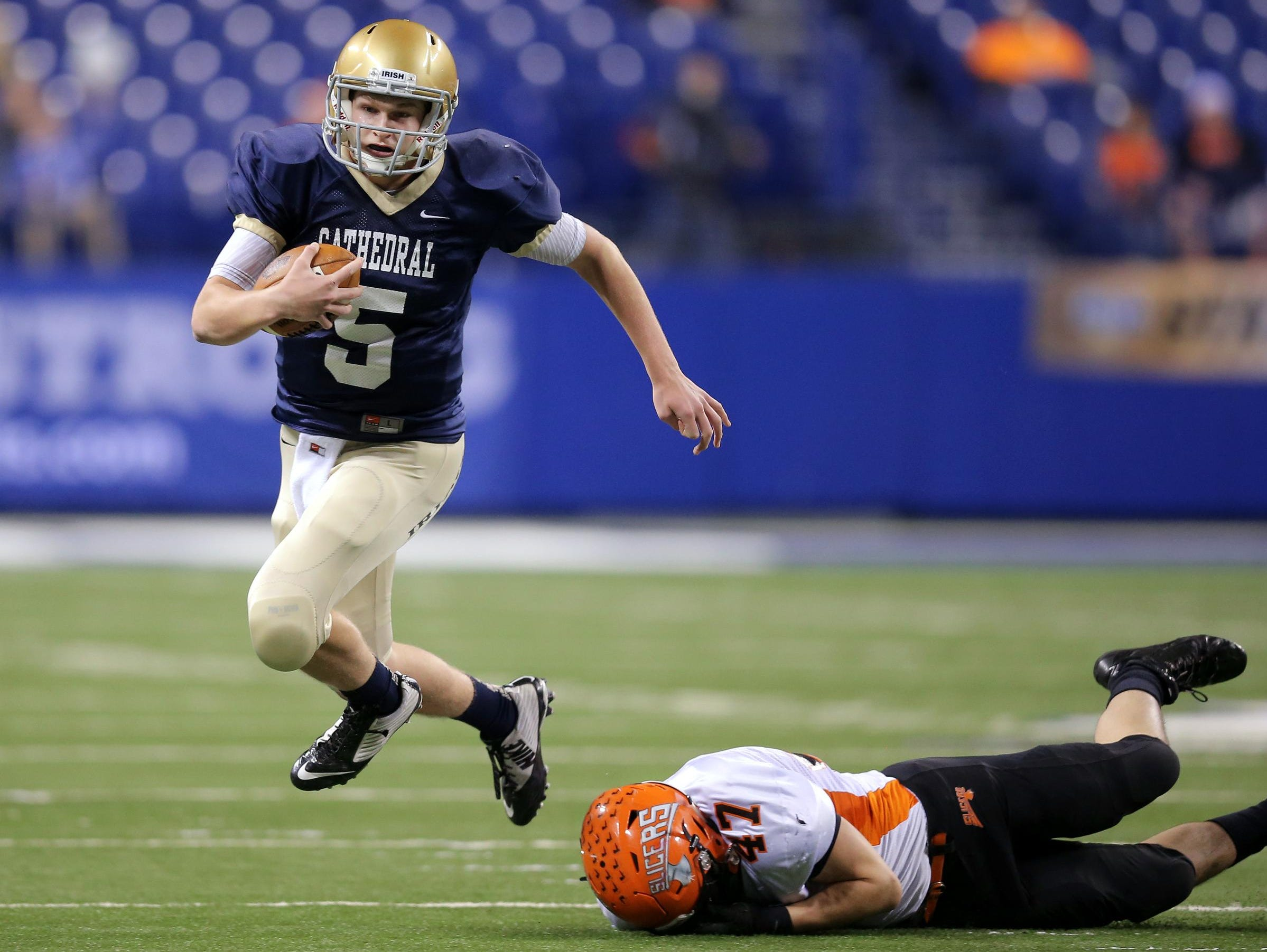 Cathedral quarterback Max Bortenschlager escapes the grasp of LaPorte linebacker Matt Otwinowski during a run in the first half of the game. The Irish defeated LaPorte 56-7 in the IHSAA Class 5A State Football Finals at Lucas Oil Stadium on Saturday, Nov. 29, 2014.