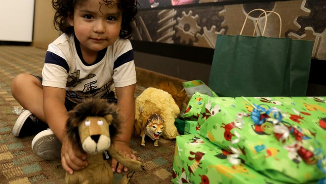 The 3-year-old son of Ever Reyes Mejia, an immigrant from Honduras shows off his plush lion in the ACLU offices in Detroit on Friday, July 13, 2018. On Tuesday, July 10 at the ICE office in Grand Rapids, he was reunited with his father after the two were separated for two months at different detention centers.