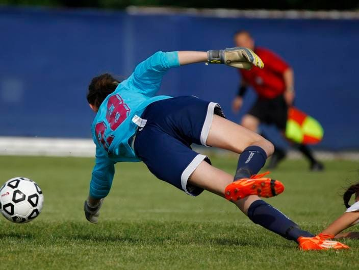 St. Johns' Lexi McPherson, right, gets the ball past East Lansing goalkeeper Madeline Chomentowski for St. Johns' first goal Thursday, at DeWitt High School.