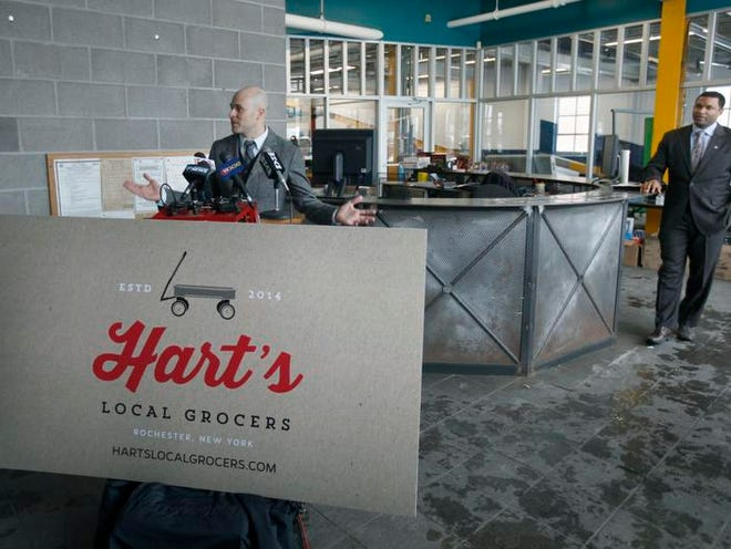 Glenn Kellogg, left, talks about Hart's Local Grocers as Delmonize Smith, the city's neighborhood and business development commissioner listens in at the store's future location on Winthrop Street.