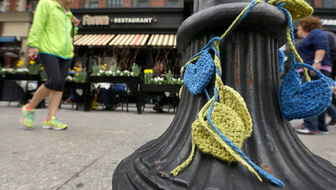 A passer-by walks past yellow and blue crocheted hearts that hang from a lamp post in front of the Forum restaurant near the finish line of the Boston Marathon Monday, April 14, 2014, in Boston. The restaurant was damaged after one of the bombs exploded in front of the building during the race April 15, 2013. (AP Photo/Steven Senne)