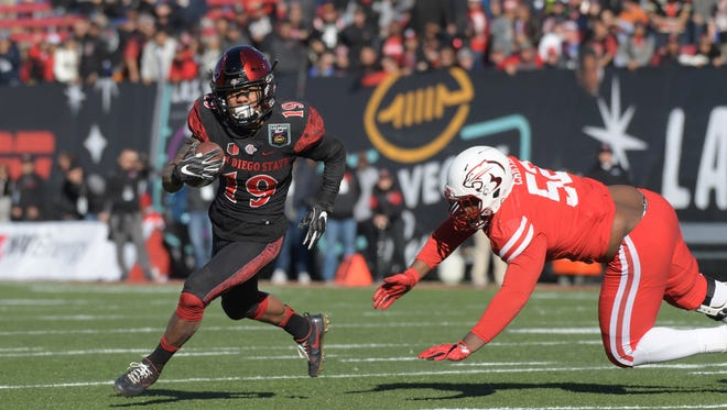 Dec 17, 2016; Las Vegas, NV, USA; San Diego State Aztecs running back Donnel Pumphrey (19) carries the ball past Houston Cougars defensive end Jerard Carter (52) during the 25th Las Vegas Bowl at Sam Boyd Stadium.
