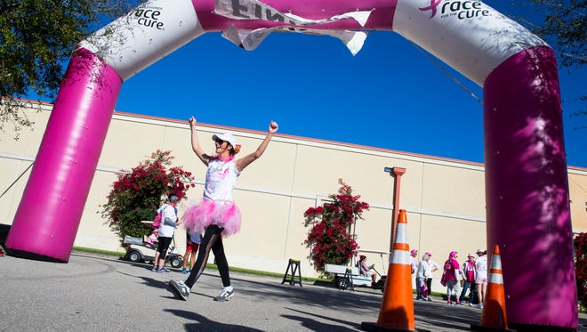 Kate Morrissey raises her arms in celebration after completing the 1 mile walk during the 11th annual Susan G. Komen Race for the Cure at Coconut Point Mall in Estero, Florida on Saturday, March 4, 2017. The event raises significant funds and awareness for the breast cancer movement, celebrates breast cancer survivorship and honors those who have lost their battle with the disease.