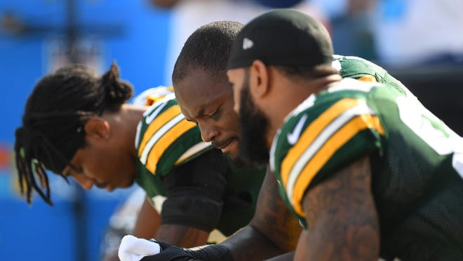 Green Bay Packers players sit in protest during the national anthem before the game against the Cincinnati Bengals at Lambeau Field on Sunday.