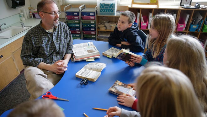 Fifth-grade students take part in a reading discussion group led by teacher Craig Piczkowski at Fairview School north of Krakow.