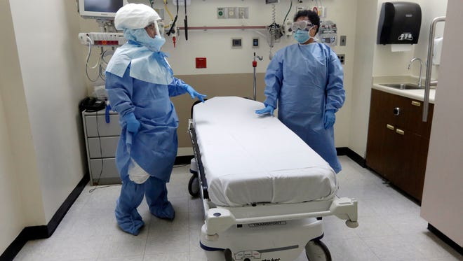 An Oct. 8 photo shows workers in protective suits at Bellevue Hospital.