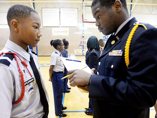 Ar'Monie Langston inspects Henry Spearman, left, during ROTC at Woodlawn High School.