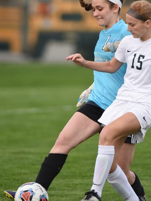 Novi's #15 pressures the Mustang goal keeper during