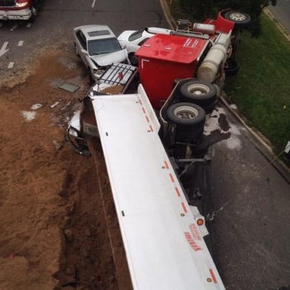 A semi-truck hauling sand lost control and flipped over on its side, dumping its load on nearby cars in Boulder Friday evening.