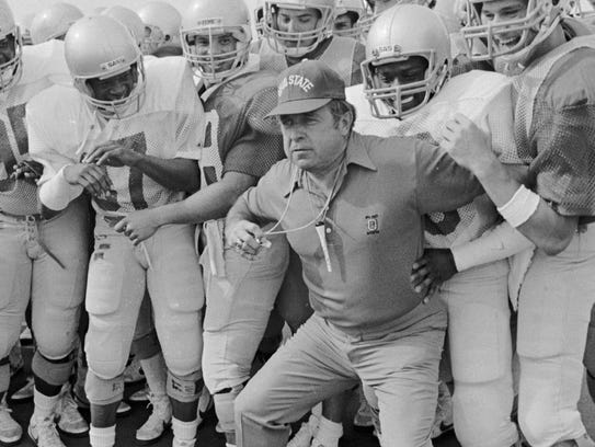 Ohio State coach Earle Bruce pushes his players backwards