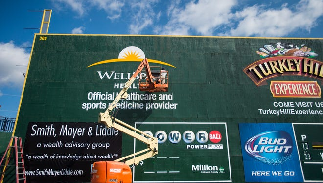 In this file photograph, Seth Winters, with Signs by Tomorrow, uses a lift to work on the signage on the left field wall above the scoreboard at PeoplesBank Park before the 2015 season. A home run net will be placed above the exterior fence surrounding the stadium, located several yards beyond the tall wall this season, in an attempt to curb the amount of damage done, specifically by home run balls during batting practice and games. The netting is expected to be about 10 feet high and 50 feet long.