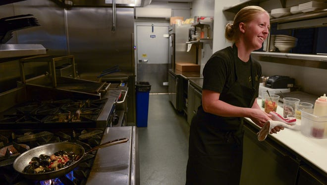 Julia Robinson, Chef de cuisine at The Blue Hen, prepares a mussel dish in the kitchen on Monday, August 7, 2017.