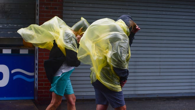 Heavy rain and winds from Potential Tropical Cyclone 10 does not keep people from walking on The Boardwalk in Ocean City, Md. Tuesday, August 29, 2017.
