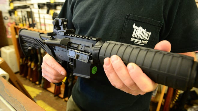 Bob Arthur, owner of Arthur's Shooters Supply, shows an example of a Maryland Compliant heavy barrel AR-15, complete with a bump stock on Thursday, Oct. 5, 2017 in Berlin, Md.