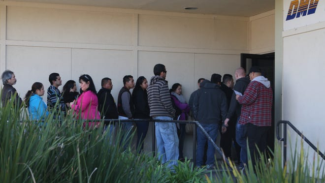 In this file photo, a line stretches outside and around the building at the California Department of Motor Vehicles in Salinas.