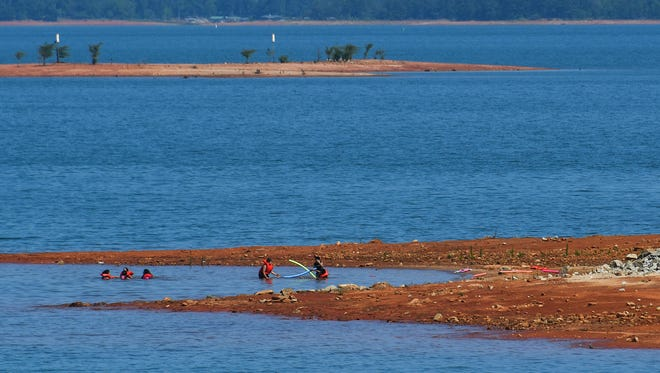 A group of swimmers play near red-clay shoreline at Singing Pines Recreation Area at Lake Hartwell in Starr. The lake is still low despite recent record rainfall in May.