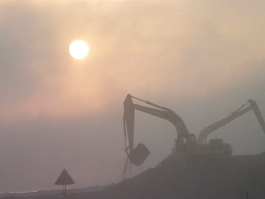 Sun reveals a cloud of coal ash above the cleanup.