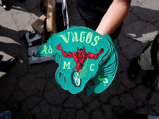 In this Oct. 6, 2011, file photo, a police officer shows Vagos motorcycle gang patches confiscated in a police raid, during a news conference at a command post in San Bernardino, Calif.