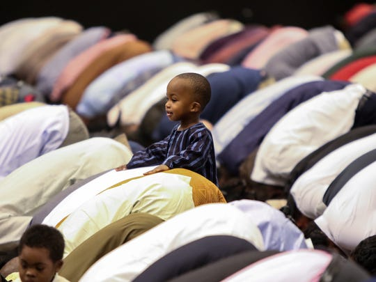Ahmad Cabbie, 2, of Wilmington, rest his hands on the back of his father, Umar, while he prayed during the Muslim holiday Eid-ul-Adha Friday morning at the Chase Center on the Riverfront in Wilmington.