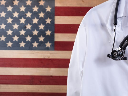 Close up of medical doctor jacket and stethoscope with flag