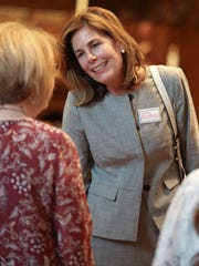 Kathy Jennings talks to an attendee after a forum of