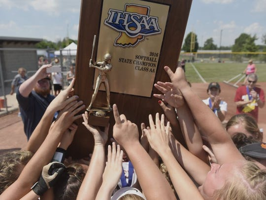 Mater Dei players get their first touch of the Class 2A state championship trophy Saturday, June 11, at Ben Davis High School in Indianapolis. Mater Dei defeated Boone Grove 1-0 to capture their its championship.