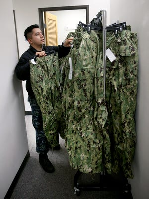 Sailor Guillermo Lopez looks through the sample pants to try on for size at the NEX store on Naval Base Kitsap-Bangor. The Navy is changing from the blue camouflage to the green.