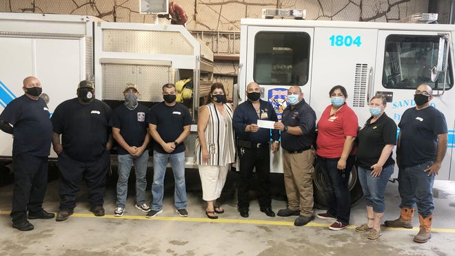 Lowe's manager Genaro Arce presents the San Diego FIre Department with a $1,500 check. Pictured (LtoR): Firefighter Joe Ochoa, Firefighter Juan Ramirez, Firefighter Alex Castillo, Firefighter Alex Tunchez, San Diego Mayor Sally Lichtenberger, Lowe's Manager Genaro Acre, San Diego Fire Chief Juan Soliz, Lowe's Store Manager Irma Gutierrez, Lowe's Employee Kimberly Carson, and Firefighter William Rangel.